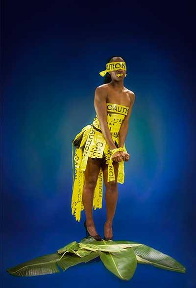 αφροαμερικανή γυναίκα τυλιγμένη με κίτρινη ταινία που γράφει caution πατάει ένα μεγάλο πράσινο φύλλο
