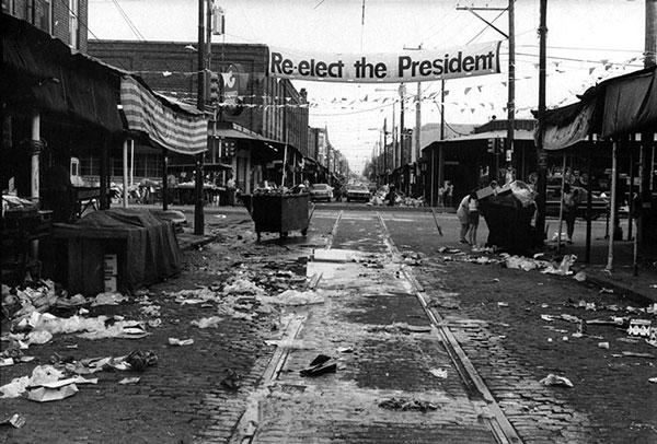 """πανό με επιγραφή """"re-elect the president"""", δρόμος και γειτονιά με σκουπίδια"""