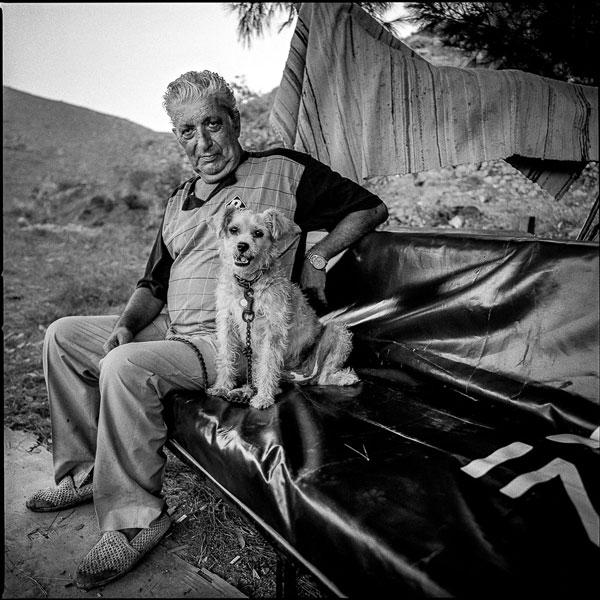 άνδρας ποζάρει καθισμενος έχοντας στο πλάιο του ένα λαυκό σκυλάκι