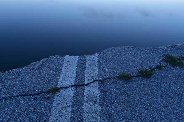 σπασμένος δρόμος με ρωγμή ο οποίος οδηγεί στη θάλασσα