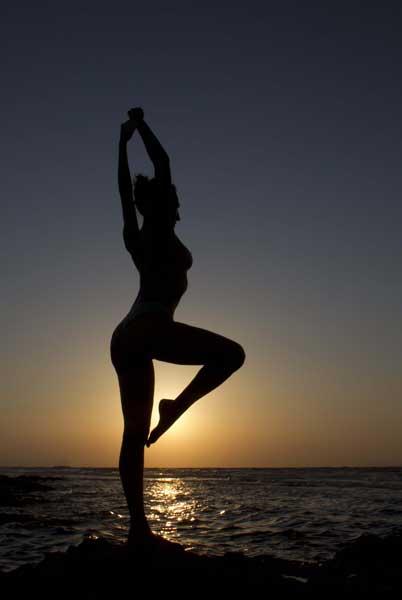γυναίκα γυμνή σε όρθια στάση με λυγισμένο το γόνατο / απο πίσω θάλασσα και ηλιοβασίλεμα