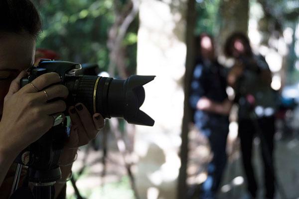 φωτογράφος κρατάει φωτογραφική μηχανή, στο βάθος 2 άλλοι φωτογράφοι