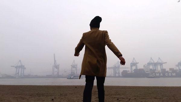 άνδρας με γυρισμένη τη πάτη στο φακό βλέπει προς το λιμάνι