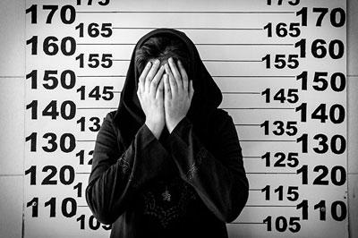 άνδρας καλύπτει το πρόσωπό του στο αστυνομικό τμήμα κατά τη διάρκεια της φωτογράφισης