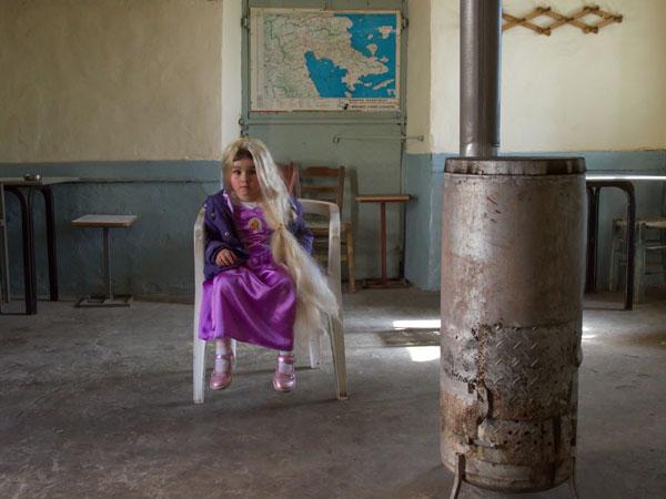 κοριτσάκι ντυμένο πριγκίπισσα καθεται σε μια πλαστική καρέκλα στη μέση ενός παλιού καφενείου