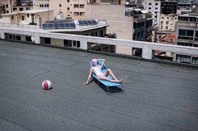 γυναίκα με μαγιώ κάνει ηλιοθεραπεία σε ταράτσα πολυκατοικίας