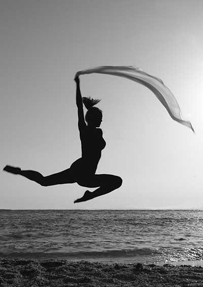 Ασπρόμαυρη φωτογραφία γυναικείας σιλουέτας που χορεύει κρατώντας ένα πέπλο