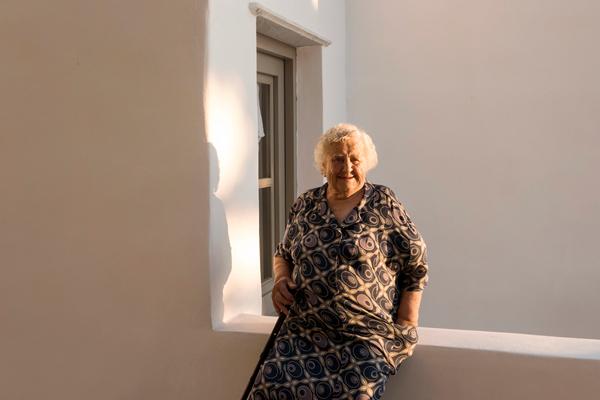 ηλικιωμένη γυναίκα καθισμένη σε βεράντα σπιτιού