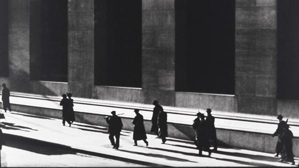 ασπρόμαυρη φωτογραφία, άνδρες ντυμένι στα μαύρα περπατάνε σε προαύλιο χώρο δημόσιου κτηρίου