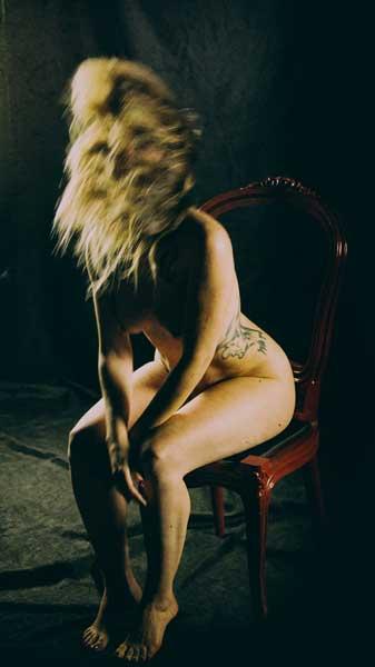 γύμνη γυναίκα με ξανθά μαλλιά και τατουάζ καθισμένη σε καρέκλα