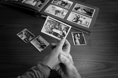 χέρια πιάνουν παλιές οικογενειακές φωτογραφίες