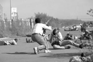 σκηνή από ταινία, παιδί κρατάει όπλο, άντρας το φωτογραφίζει