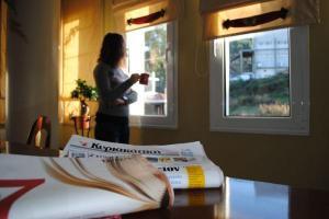 εφημερίδα, γυναίκα πίνει καφέ και κοιτάει από παράθυρο