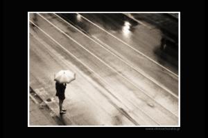 γυναίκα ντυμένη στα μαύρα κρατάει ομπρέλα στην άκρη ενός δρόμου