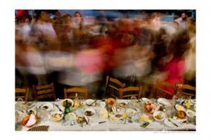τραπέζι με εδέσματα και άδειες καρέκλες, άνθρωποι που χορεύουν