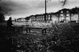 ασπρόμαυρη φωτογραφία, άνδρας κάθεται σε παγκάκι σε κήπο επιβλητικού κτιρίου