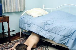 γυναίκα ημίγυμνη εξω από το κρεβάτι, η μισή σκεπασμένη