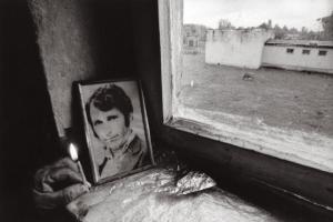 φωτογραφία νεκρού άνδρα δίπλα σε παράθυρο και ένα καντήλι αναμμένο