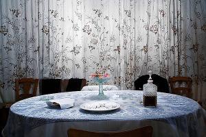 κουρτίνα, στρωμένο τραπέζι, μπουκάλι με ποτό, καρέκλες, γλυκά