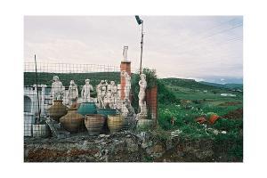 περιφραγμένος χώρος σε κάποιο χωράφι με αγαλματάκια και πύλινες γλάστρες
