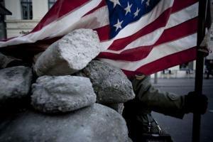 στρατιώτης κρατάει την αμερικανική σημαία, πέτρες