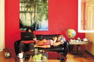 ζευγάρι καθισμένο στον καναπέ / η γυναίκα κοιμάται / ο άνδρας εργάζεται στον υπολογιστή