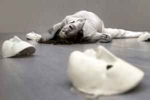 ηθοποιίος πεσμένη στο πάτωμα και δίπλα της 3 άσπρες γύψινες μάσκες