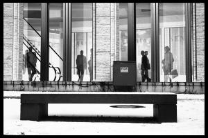 σιλουέτες ανθρώπων ανταλακλούνται πάνω σε τζάμι εμπορικού κτιρίου