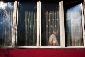 ηλικιωμένη γυναίκα κοιτάζει μέσα από το παράθυρο του σπιτιού της