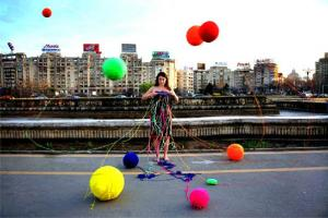 γυναίκα φοράει ένα περίεργο ρούχο από το οποίο κρέμονται μπαλόνια