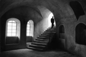 μοναχός ανεβαίνει τα σκαλιά στο εσωτερικό κάποιου μοναστηριού
