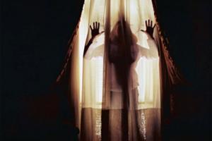 σκιά γυναίκας πίσω από κουρτίνα