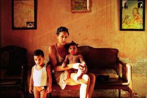 γυναίκα ποζάρει καθισμένη σε έναν καναπέ με τα δύο της παιδιά