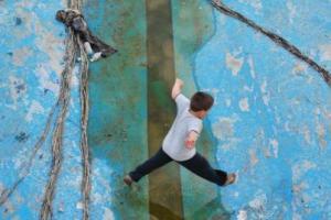 παιδί πηδάει πάνω από στάσιμο νερό