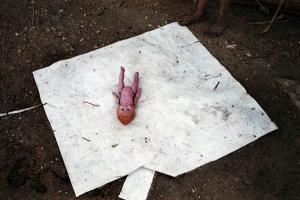 κούκλα πάνω σε λευκό λερωμένο πανί
