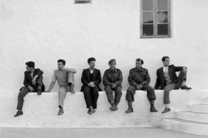 άνδρες κάθονται στο πεζούλι ενός κτηρίου