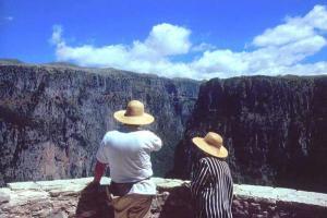 δύο τουρίστες με ψάθινα καπέλα θαυμάζουν τη θέα