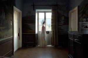 γυναικεία φιγούρα με άσπρο μακρύ φόρεμα προχωράει μπροστά απο ενα παράθυρο