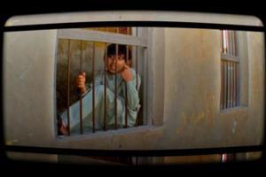 φωτογραφία απο απόσπασμα video / παιδί πίσω από κάγκελα σπιτιού