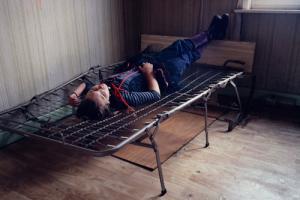 κορίτσι ξαπλωμένο σε κρεβάτι χωρίς στρώμα