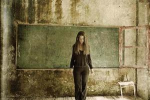γυναίκα στέκεται μπροστά από πράσινο πίνακα σχολικής αίθουσας