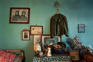 εσωτερικό παλιού σπιτιού, παλιές φωτογραφίες σε κάδρα, ένα σακάκι κρεμασμένο στο τοίχο