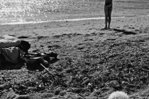 ασπρόμαυρη φωτογραφία, άνδρας κάνει διατάσεις σε παραλία, σκύλος