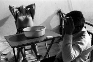γυναίκα πιάνει το κεφάλι της/ άντρας κρατάει τσιγάρο με το χερι ακουμπισμένο στο κεφάλι