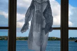 φόρεμα κρεμασμένο σε παράθυρο με θέα τη θάλασσα