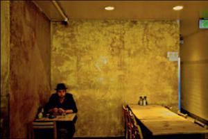 άντρας κάθεται σε τραπέζι άδειου μπαρ