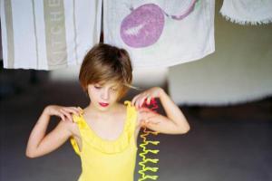 κοριτσι με κίτρινο μαγιώ κάνει μία χορευτική φιγούρα, πετσέτες