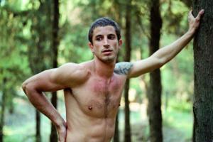 νεαρός άντρας ακουμπάει το χέρι του σε κορμό δέντρου