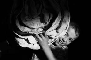 παιδί χαμογελάει σηκώνοντας πάπλωμα