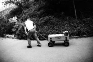 ασπρόμαυρη φωτογραφία, παιδί τραβάει φορτηγάκι